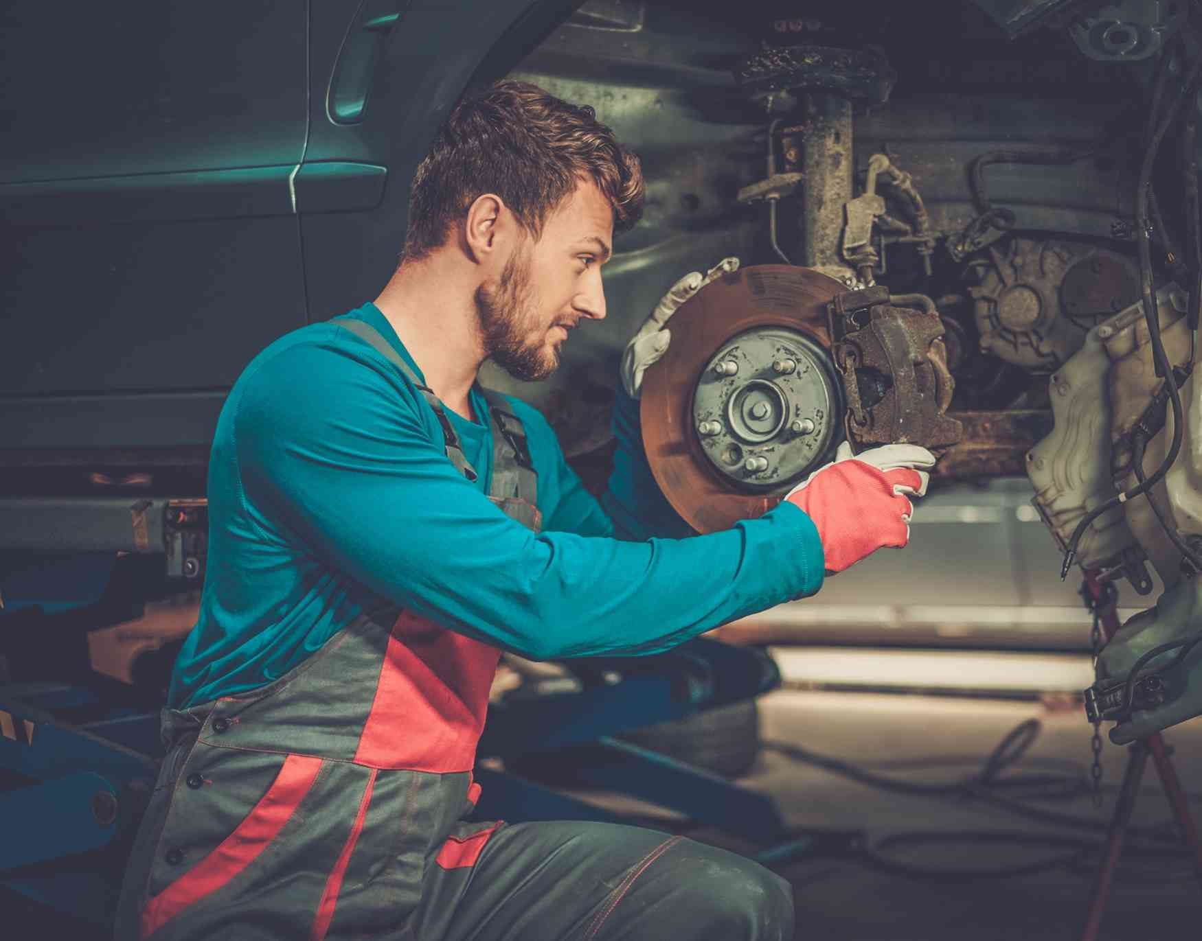 mechanic-checking-car-brake-system-in-a-workshop